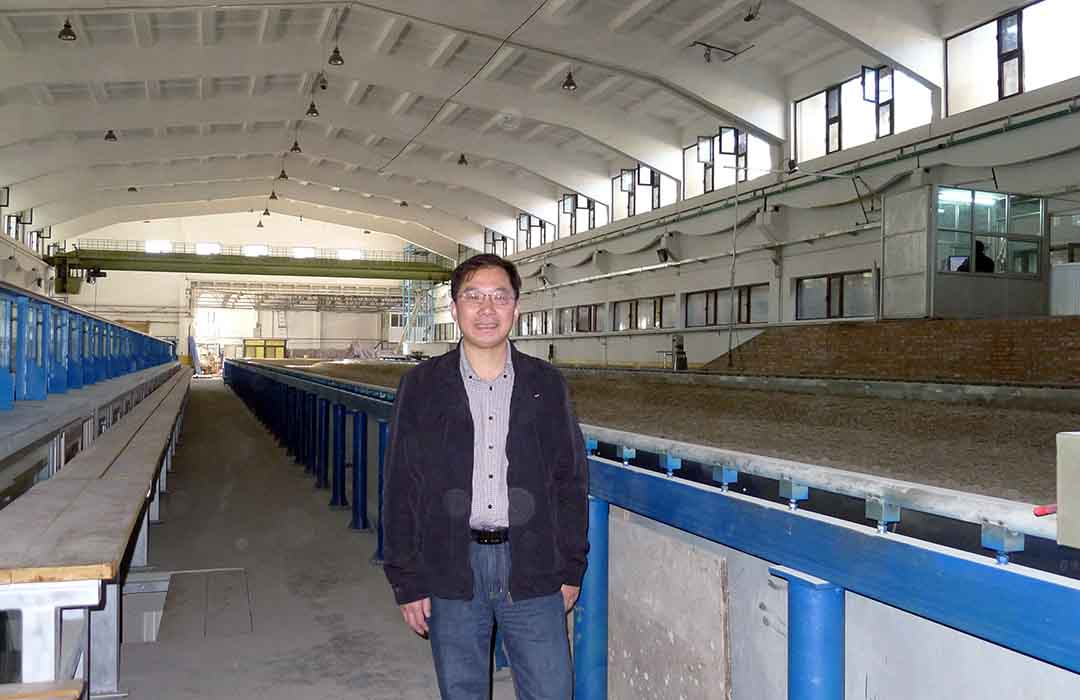 Prof. Qicheng SUN stands in front of a particle transportation testing facility during a September 2013 ATIP visit to the State Key Lab of Hydroscience and Engineering of Tsinghua University in China.